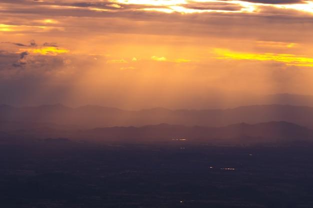 Toneelmening van silhouetbergen tegen hemel tijdens zonsondergang en straal Premium Foto