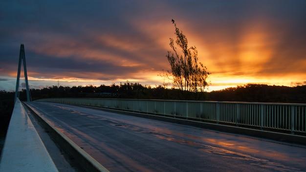Toneelschot van een zonsondergang vanaf een brug met mooie stralen die van de zon uitstralen Gratis Foto
