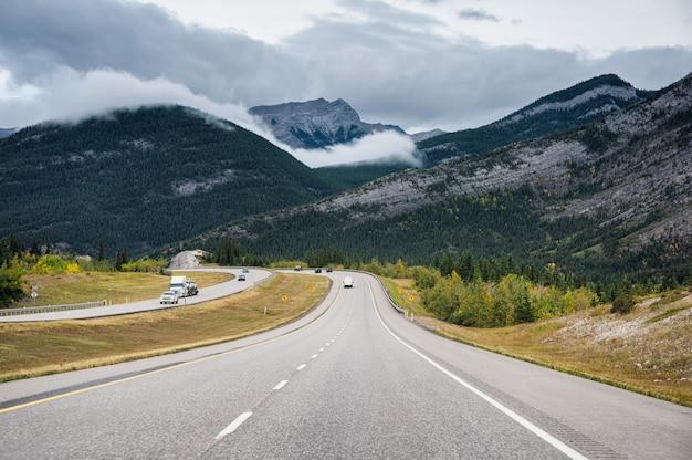 Toneelwegreis met rotsachtige berg in de herfstbos bij het nationale park van banff Premium Foto