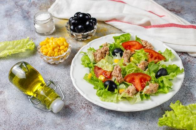 Tonijnsalade met sla, olijven, maïs, tomaten, bovenaanzicht Gratis Foto