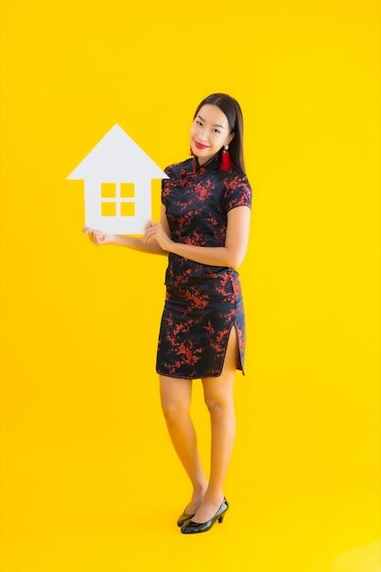 Toont de chinese kleding van de portret mooie jonge aziatische vrouw slijtage huisteken Gratis Foto