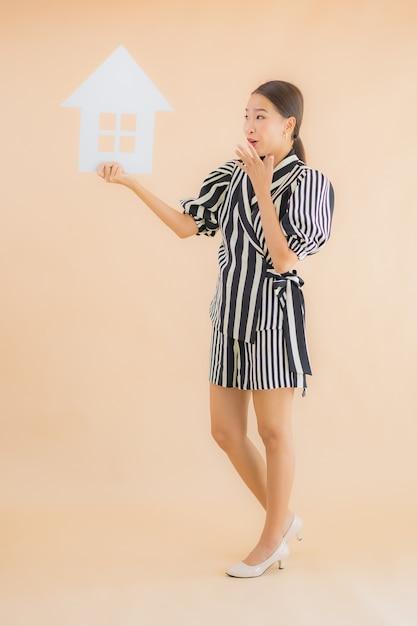 Toont de portret mooie jonge aziatische vrouw huis of huisdocument teken Gratis Foto