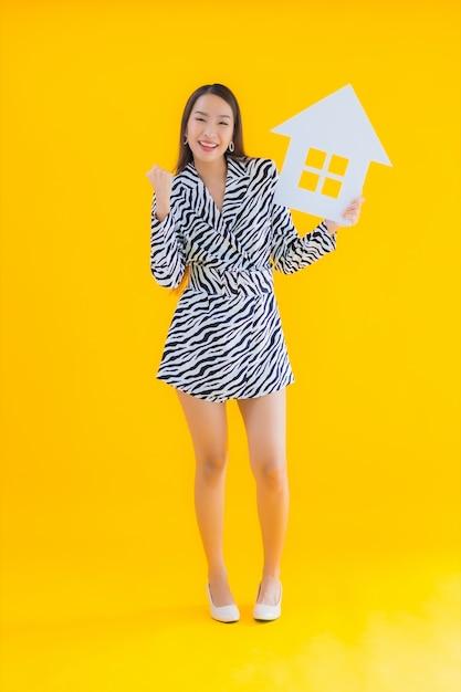 Toont de portret mooie jonge aziatische vrouw huis of huisteken op geel Gratis Foto
