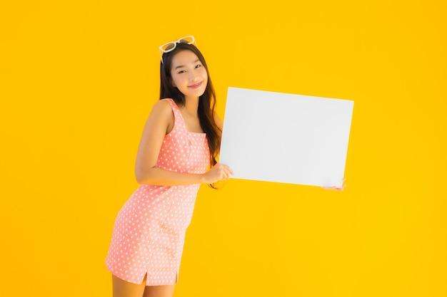 Toont de portret mooie jonge aziatische vrouw leeg wit aanplakbiljet Gratis Foto
