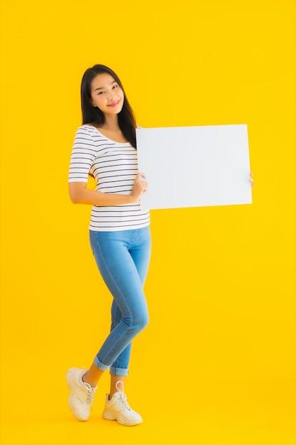 Toont de portret mooie jonge aziatische vrouw leeg wit aanplakbordteken Gratis Foto