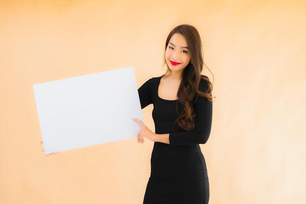 Toont de portret mooie jonge aziatische vrouw lege witte raad Gratis Foto
