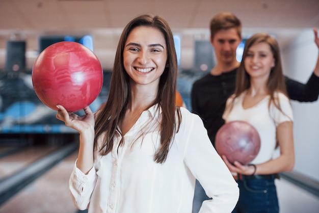 Toothy glimlach. jonge vrolijke vrienden vermaken zich in het weekend in de bowlingclub Gratis Foto