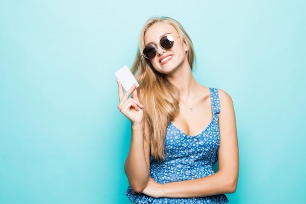 Toothy glimlachende jonge vrouw in zonnebril houdt creditcard op blauwe achtergrond. Gratis Foto