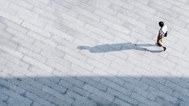 Top luchtfoto man lopen op over voetgangers beton met zwart silhouet. Premium Foto