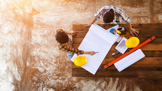 [top view construction teamwork] team van ingenieurs en architecten die werken, vergaderen, bespreken, ontwerpen, schaven, lay-out meten van het bouwen van blauwdrukken op de bouwplaatsvloer in de fabriek. Premium Foto