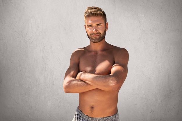Topless knappe macho man met gekruiste handen, voelt zijn kracht en vertrouwen poseren voor de camera Gratis Foto