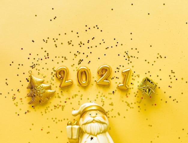 Toy santa claus met een geschenkdoos in gouden kleur en de inscriptie 2021 op een gele achtergrond vakantieconcept, bovenaanzicht, kopieer ruimte. Gratis Foto