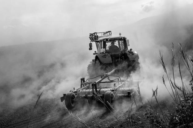 Tractor die een stoffig gebied ploegt Premium Foto