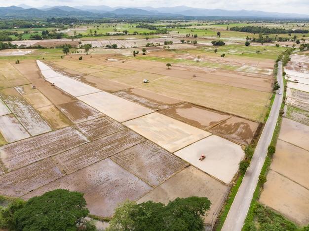 Tractor die grond op overstroomd padiegebied voorbereiden voor rijstinstallatie Premium Foto