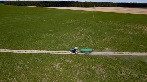 Tractor met aanhangwagenbemestingsveld met natuurlijke mest Premium Foto