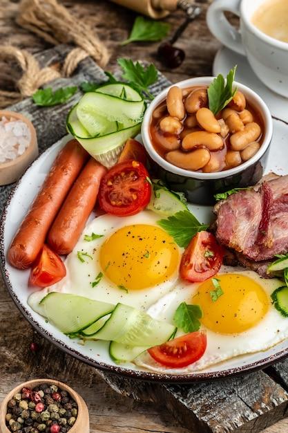 Traditioneel engels ontbijt met gebakken eieren, spek, bonen, koffie en worst, restaurantmenu, dieet, kookboekrecept. verticaal beeld. Premium Foto