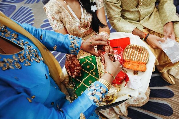 Traditioneel indisch huwelijksritueel met het zetten van armbanden Gratis Foto