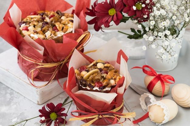 Traditioneel russisch pasen-kwarkdessert, orthodoxe paskha op grijze concrete lijst met kulichcakes, bloemen, gekleurde eieren. Premium Foto