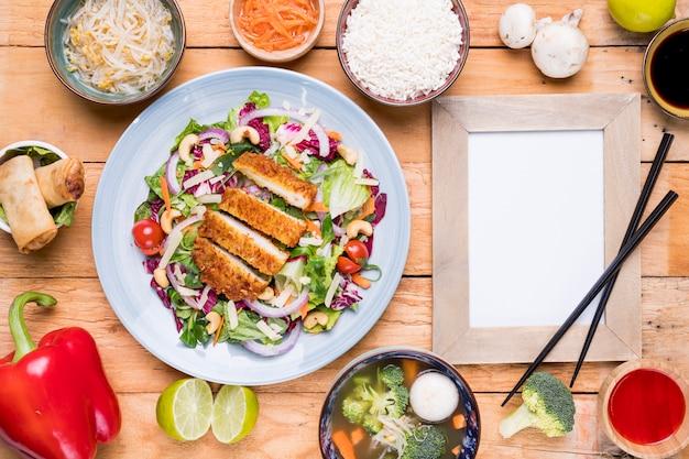 Traditioneel thais voedsel met lege omlijsting en eetstokjes op houten lijst Gratis Foto