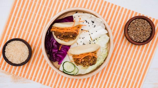 Traditioneel voedsel gua bao in stoomboot met salade op placemat Gratis Foto
