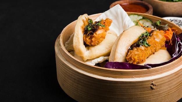 Traditioneel voedsel van taiwan gua bao in stoomboot tegen zwarte achtergrond Gratis Foto