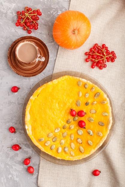 Traditionele amerikaanse zoete pompoenpastei die met meidoorn rode bessen en pompoenzaden wordt verfraaid met kop van koffie op een grijs beton. bovenaanzicht, close-up. Premium Foto