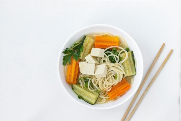 Traditionele aziatische soep met tofu kaas, noedels, wortelen en courgette op witte achtergrond Premium Foto