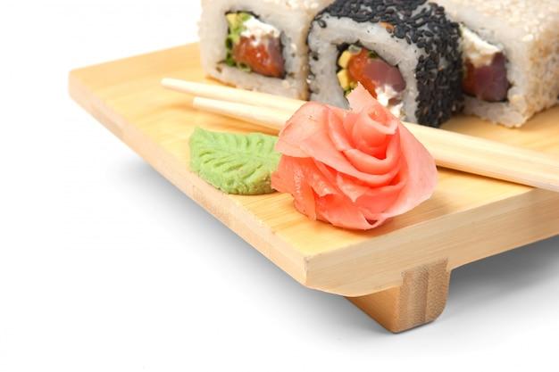 Traditionele aziatische voedselsushi op houten geïsoleerde plaat Premium Foto