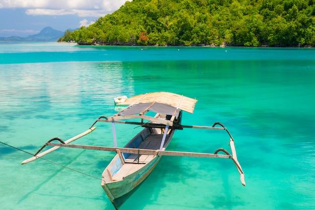 Traditionele boot die op de transparante blauwe gestemde lagune van de verre togean eilanden, indonesië drijven. Premium Foto