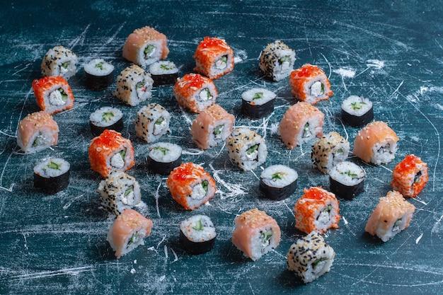 Traditionele geassorteerde sushibroodjes op blauw. Gratis Foto