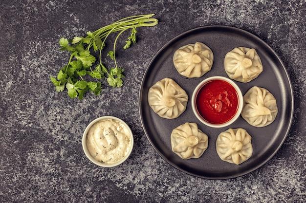 Traditionele gestoomde knoedels khinkali met tomaat en tartaarsaus Premium Foto