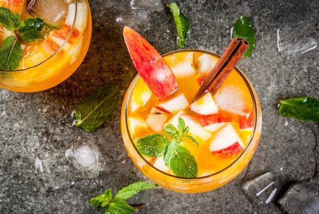 Traditionele herfstdranken, appelcider mojito-cocktails met munt, kaneel en ijs. op zwarte stenen tafel, bovenaanzicht Premium Foto
