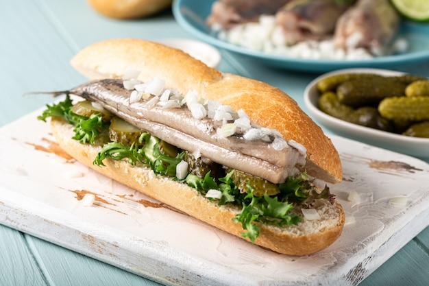 Traditionele hollandse snack, sandwich met zeevruchten, haring, uien en ingelegde komkommer. broodje haring. detailopname Premium Foto