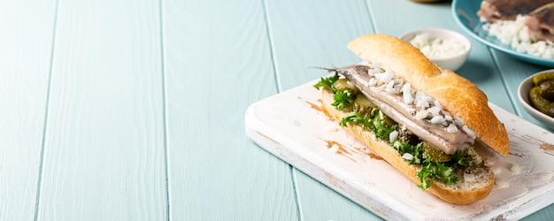 Traditionele hollandse snack, sandwich met zeevruchten, haring, uien en ingelegde komkommer. broodje haring, kopieerruimte, banner Premium Foto