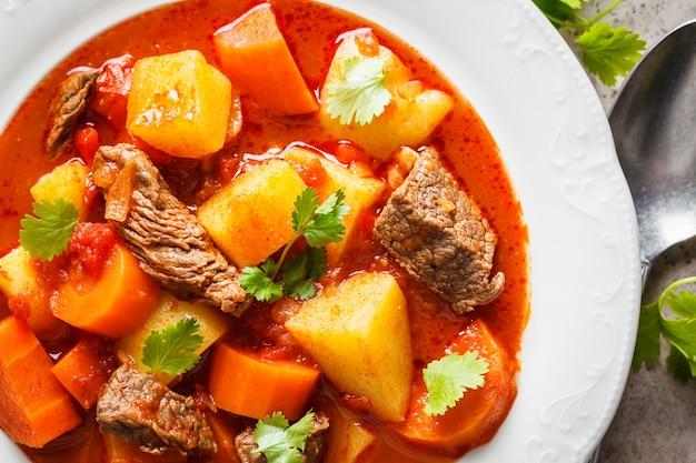 Traditionele hongaarse goulash. rundvleeshutspot met aardappels, wortelen en paprika in witte plaat, hoogste mening. Premium Foto