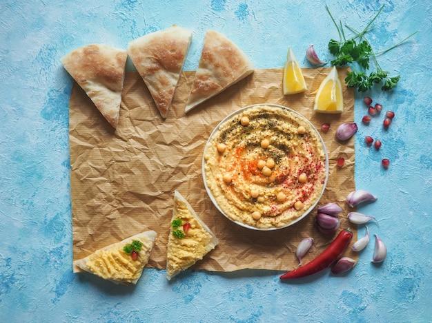 Traditionele hummus en gebroken broodkorrel op perkament. Premium Foto