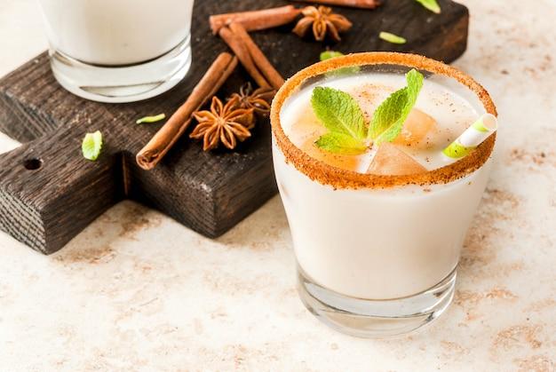 Traditionele indiase drank is ijsthee of chai masala, met ijsblokjes van chai, melk en muntblaadjes. met gestreepte rietjes, op een houten bord. op licht beige stenen tafel. copyspace Premium Foto