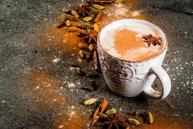 Traditionele indiase masala chai thee met kruiden kaneel, kardemom, anijs, donkere steen. copyspace Premium Foto
