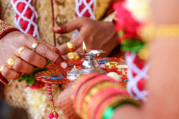 Traditionele indische huwelijksceremonie, de bruidhand van de bruidegomholding Premium Foto