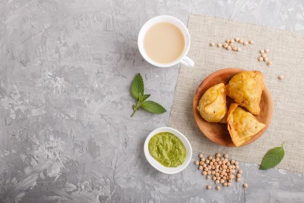 Traditionele indische voedselsamosa in houten plaat met muntchutney op een grijs beton copyspace. bovenaanzicht. Premium Foto