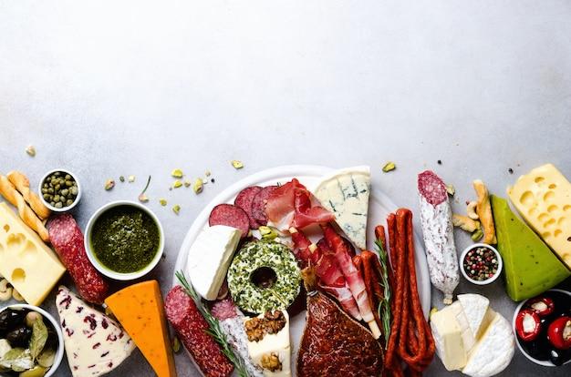 Traditionele italiaanse antipasto, snijplank met salami, koudgerookt vlees, prosciutto, ham, kaas, olijven, kappertjes op grijs. Premium Foto