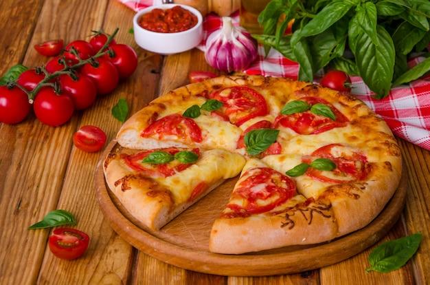 Traditionele italiaanse pizzamargarita met tomaten en mozzarellakaas Premium Foto