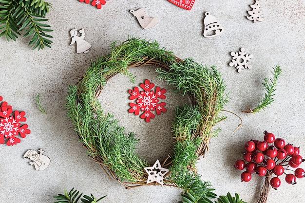Traditionele kerstkrans met decoratieve bessen en houten kerstmisspeelgoed Premium Foto