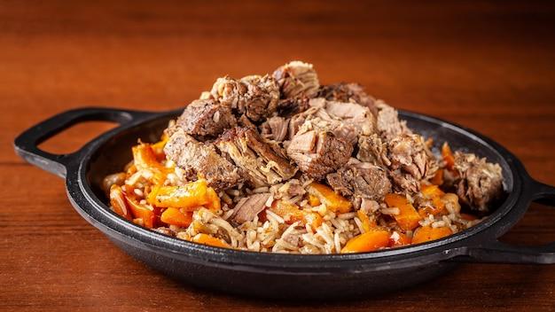 Traditionele oezbeekse oosterse keuken, pilaf of plov met grote stukken lamsvlees en wortelen, gekookt in een zwarte gietijzeren koekepan van kazan. Premium Foto