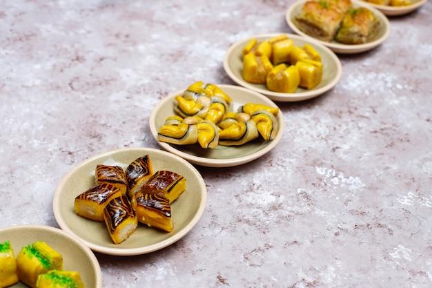 Traditionele oosterse snoepjes met verschillende noten op concrete oppervlakte, hoogste mening, exemplaarruimte Gratis Foto