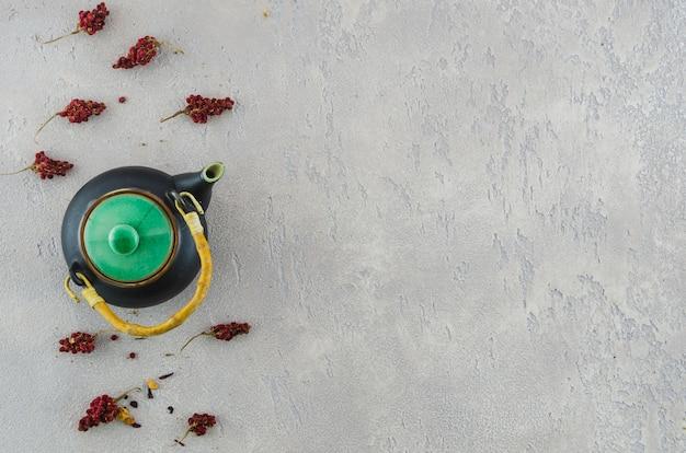Traditionele oosterse theepot met gedroogde bloemen kruiden op grijze gestructureerde achtergrond Gratis Foto