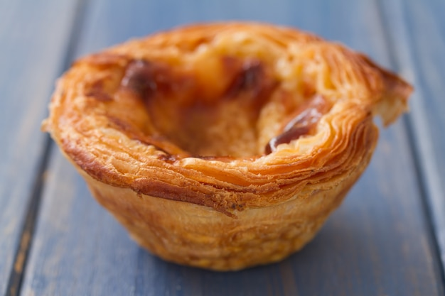 Traditionele portugese koekjes pasteis de nata op blauwe houten oppervlakte Premium Foto