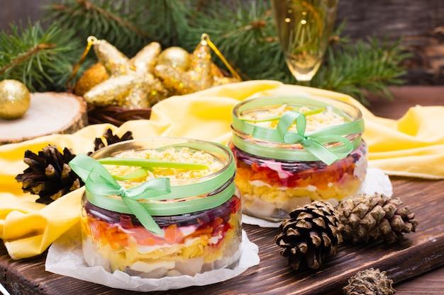 Traditionele russische salade, haring onder een bontjas in kommen in de decoraties van het nieuwjaar Premium Foto