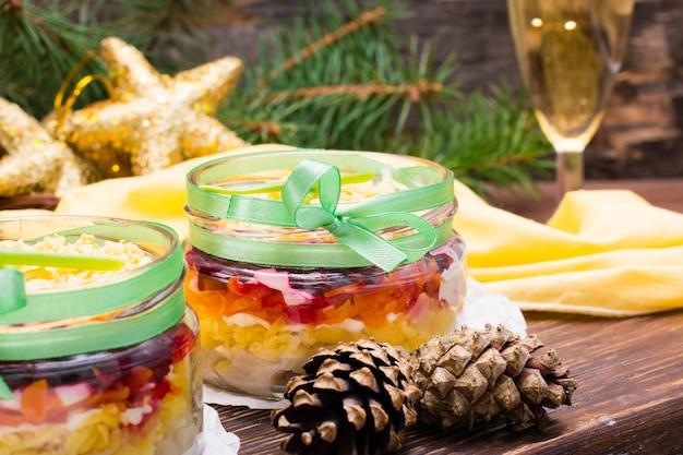 Traditionele russische salade, haring onder een bontjas in kommen Premium Foto