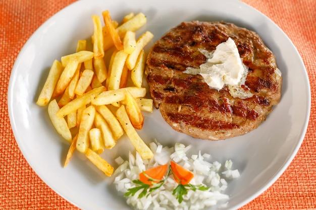 Traditionele servische pljeskavica geserveerd met frietjes Premium Foto